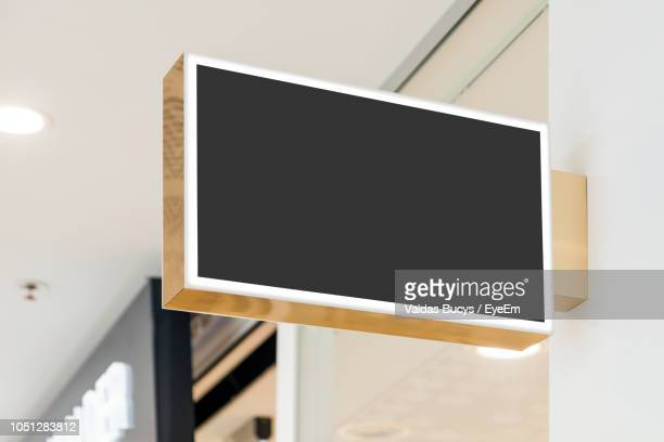 low angle view of blank signboard attached to wall - manifesto foto e immagini stock