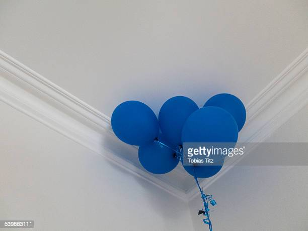 Low angle view of blue balloons against ceiling at home