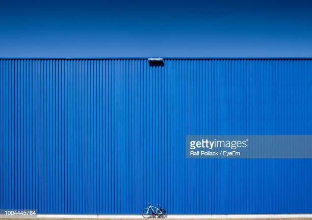 low angle view of blue container against clear sky - corrugated iron stock photos and pictures