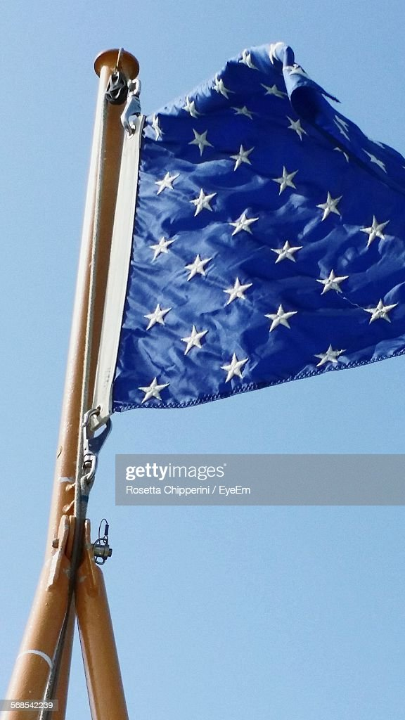 Low Angle View Of Blue Flag Flying Against Clear Sky : Stock Photo
