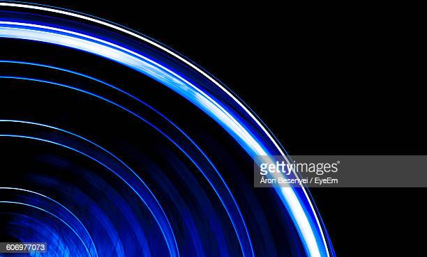 Low Angle View Of Blue Illuminated Spinning Ferris Wheel
