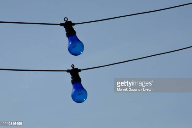 Low Angle View Of Blue Light Bulbs Hanging Against Clear Blue Sky