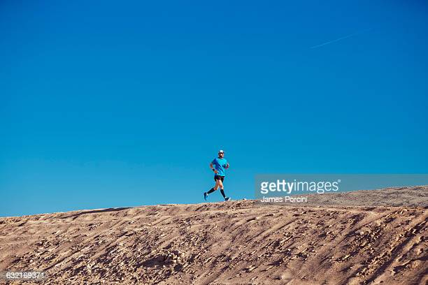 Low angle view of blue sky and mid adult man running on sand dune, Dubai, United Arab Emirates