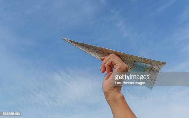low angle view of blue sky and womans hand holding paper airplane made from map - aerodinâmico - fotografias e filmes do acervo