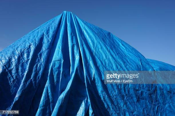 Low Angle View Of Blue Tarpaulin Cover Against Clear Sky