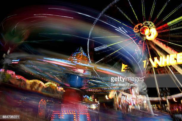 Low Angle View Of Blurred Rides At Night