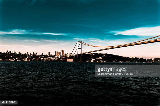 Low Angle View Of Bosphorus Bridge Over River In City Against Cloudy Blue Sky