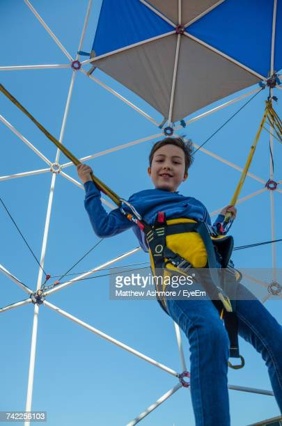 Low Angle View Of Boy Bungee Jumping Against Clear Sky