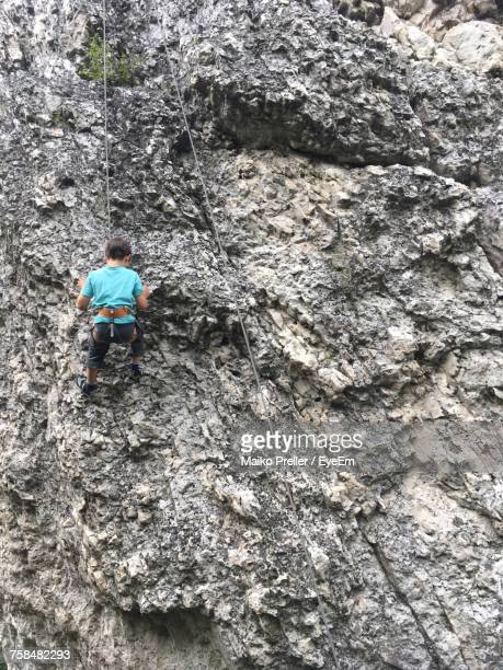 Low Angle View Of Boy Climbing Rock Formation At Viechtach