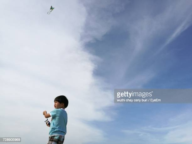 Low Angle View Of Boy Flying Kite Against Cloudy Sky