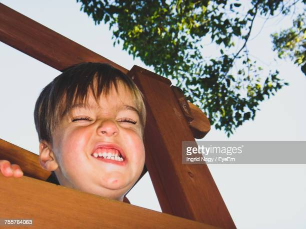 Low Angle View Of Boy Grimacing In Wooden Structure