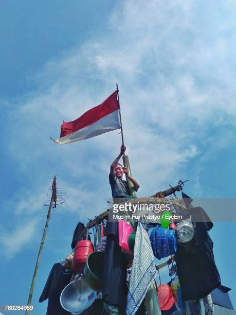 low angle view of boy holding indonesian flag on market stall against sky - indonesia flag stock photos and pictures