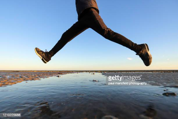low angle view of boy jumping - winning stock pictures, royalty-free photos & images