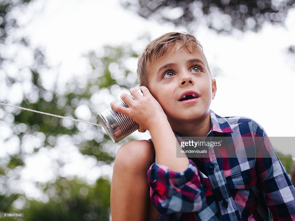 Low angle view of Boy listening on tin can phone : Stock Photo