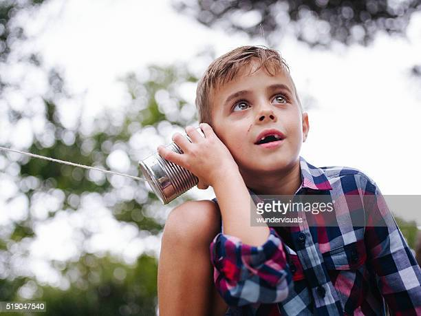 Low angle view of Boy listening on tin can phone