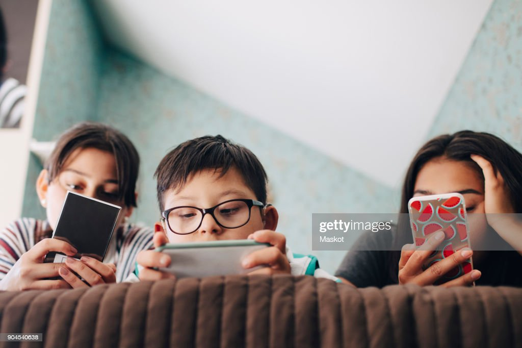Low angle view of boy looking at digital tablet while lying with sisters using mobile phone on bed at home : Stock Photo