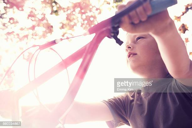 Low angle view of boy on BMX bicycle looking away
