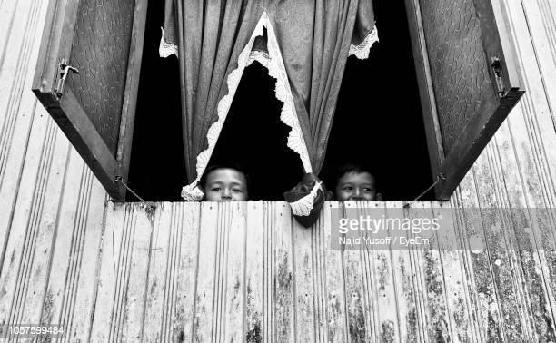 low angle view of boy peeking though window - najid yusoff stock pictures, royalty-free photos & images