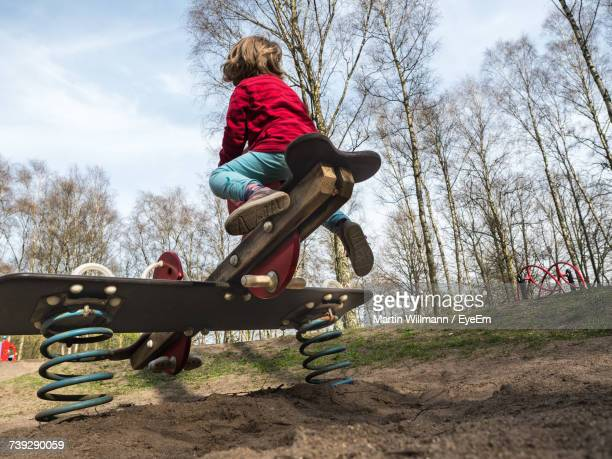 Low Angle View Of Boy Playing On Seesaw At Playground