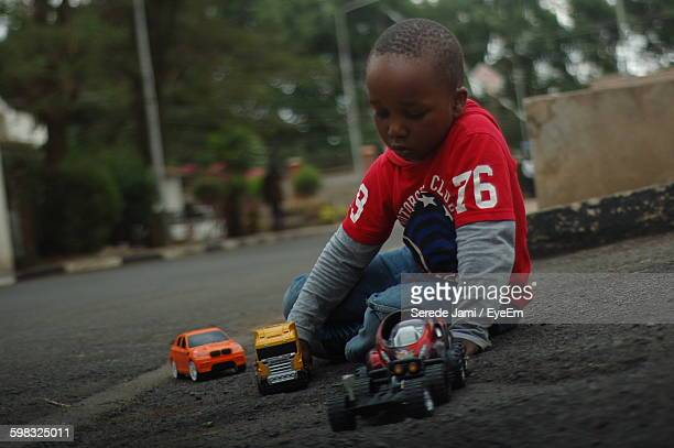 Low Angle View Of Boy Playing With Toy Car On Street