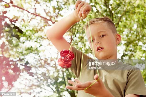 Low angle view of boy playing with yo-yo looking down