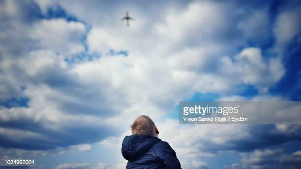 low angle view of boy standing against cloudy sky - guardare in su foto e immagini stock