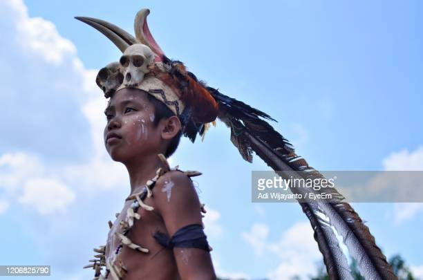 low angle view of boy wearing headdress against sky - マイノリティ ストックフォトと画像