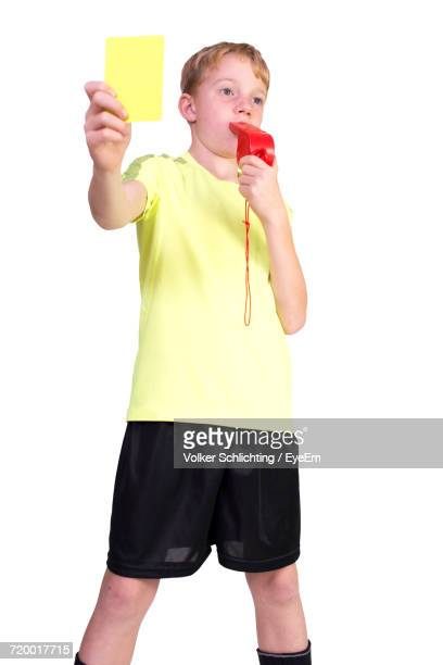 low angle view of boy whistling and showing yellow card against white background - oficial deportivo fotografías e imágenes de stock