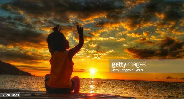 Low Angle View Of Boy With Arms Raised Sitting At Beach Against Sky During Sunset