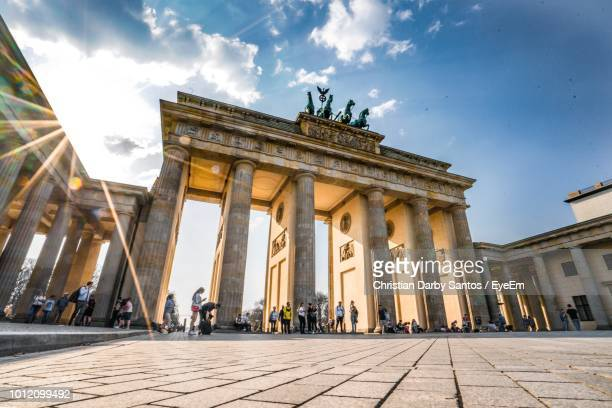 low angle view of brandenburg gate against blue sky - berlin stock-fotos und bilder