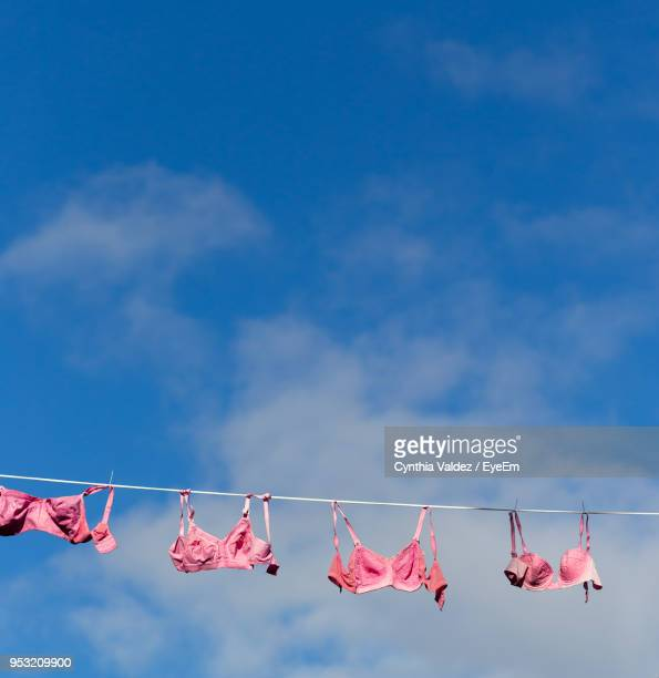 low angle view of bras hanging on clothesline against sky - bras stock pictures, royalty-free photos & images