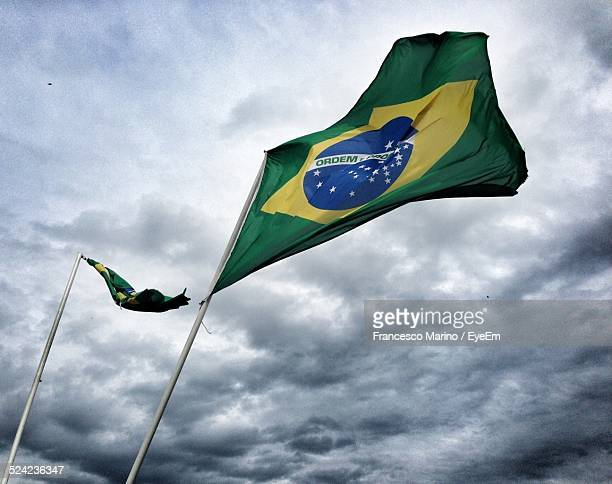 Low Angle View of Brazilian Flags Against Cloudy Sky