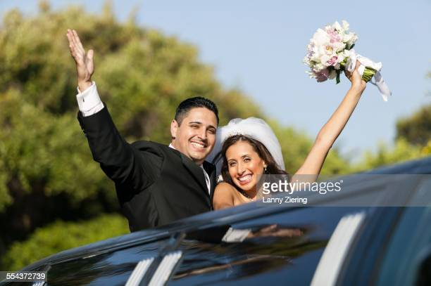 low angle view of bride and groom cheering in limousine sunroof - limousine stock pictures, royalty-free photos & images