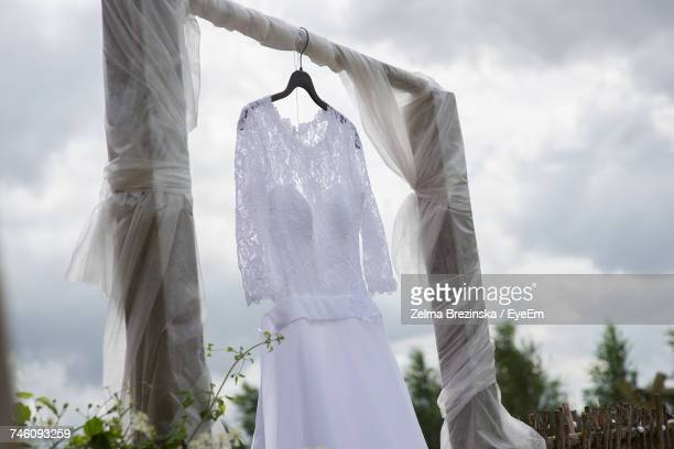 Low Angle View Of Bride Dress Hanging On Wood Against Cloudy Sky