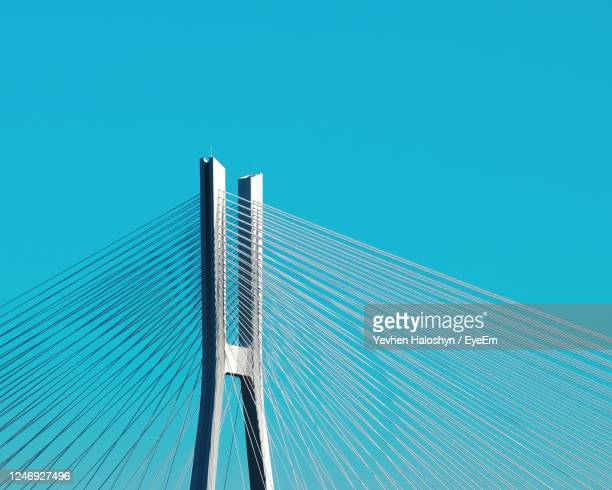 low angle view of bridge against blue sky - suspension bridge stock pictures, royalty-free photos & images