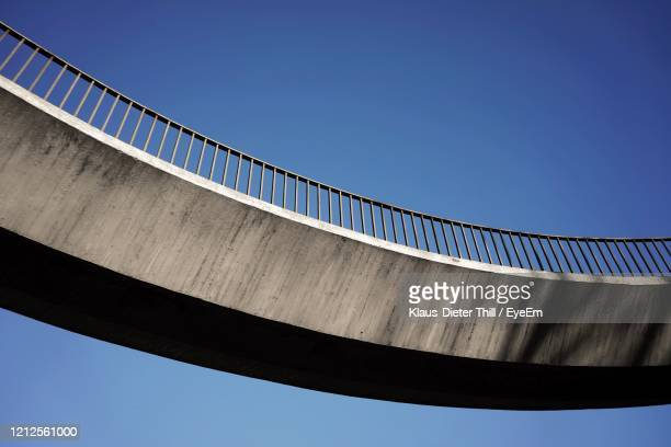 low angle view of bridge against clear blue sky - klaus-dieter thill stock-fotos und bilder