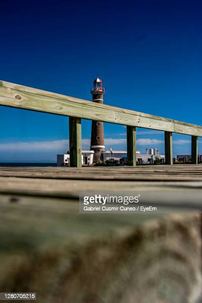 low angle view of bridge against clear blue sky with lighthouse - jose ignacio lighthouse stock pictures, royalty-free photos & images