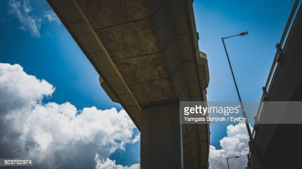 Low Angle View Of Bridge Against Cloudy Sky In City