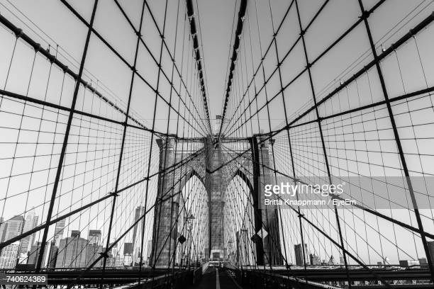 low angle view of bridge against sky - brooklyn bridge stock pictures, royalty-free photos & images
