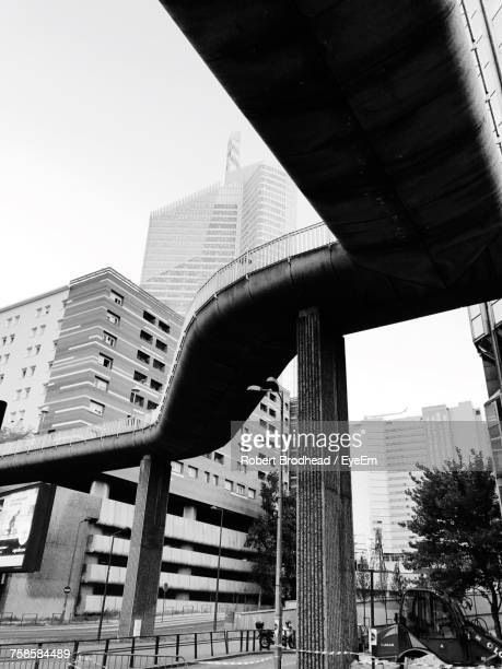 Low Angle View Of Bridge By Buildings In City