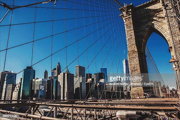 low angle view of bridge cables with buildings against blue sky - noemi foto e immagini stock