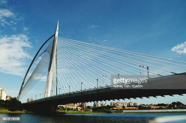 low angle view of bridge over river against blue sky - putrajaya stock photos and pictures