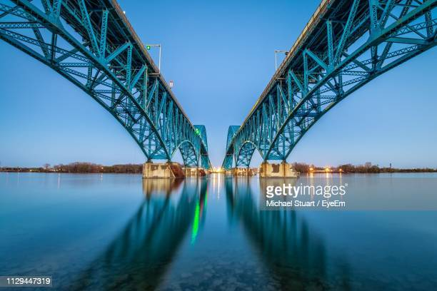 low angle view of bridge over river against clear sky during sunset - symmetry stock pictures, royalty-free photos & images