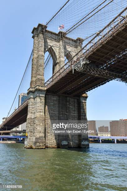 low angle view of bridge over river against clear sky - brooklyn bridge stock pictures, royalty-free photos & images