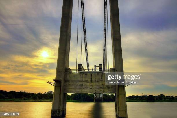 Low Angle View Of Bridge Over River Against Sky During Sunset