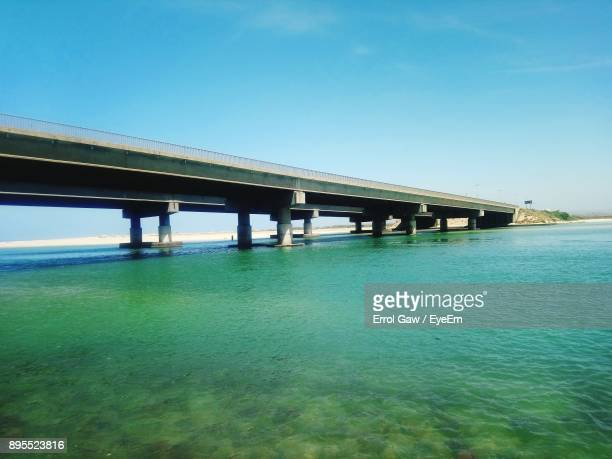 Low Angle View Of Bridge Over Sea Against Clear Blue Sky