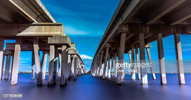 low angle view of bridge over sea against sky, cape canaveral, united states - cape canaveral stock pictures, royalty-free photos & images