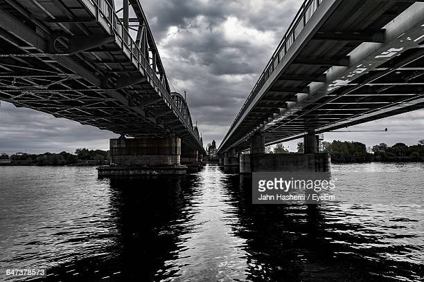 Low Angle View Of Bridges On River Against Cloudy Sky