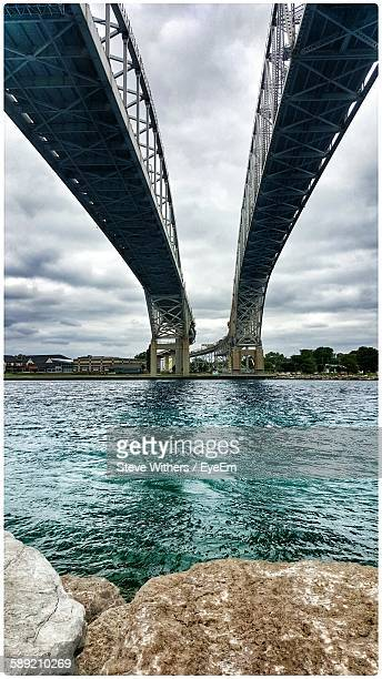 low angle view of bridges over river against cloudy sky - サルニア ストックフォトと画像