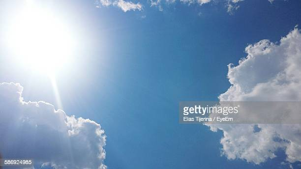 Low Angle View Of Bright Sun In Blue Sky